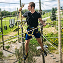 Man climbing through an elevated adventure ropes course on a sunny day.