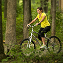 Woman riding a bike through the woods in the summer.