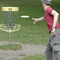 Man throwing a Frisbee into a Disc Golf goal.