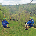 Two friends going down a 3,000' dual zip line next to each other.