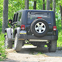 Back of a black Jeep® going off-road into the woods.