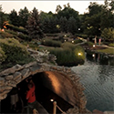 Scenery around a mini golf course with water and rock features and a tunnel.