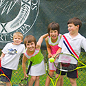 Children laughing with tennis rackets.