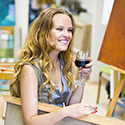 Woman smiling with wine holding a painting canvas.
