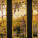 Stained glass featuring an outdoor landscape of vines and hills.