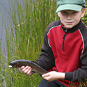 Boy with fish during his Junior Outdoorsman outing.