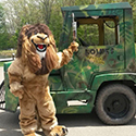 Lion mascot waving in front of a jungle-painted train.
