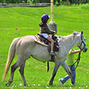 A child being led by an adult on a grey pony.