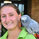 Girl with grey African parrot on her shoulder.