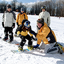 Snowboard instructor assisting a young child in a lesson.