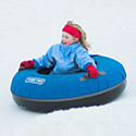 Young girl riding down a hill in a blue snow tube.