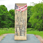 Piece of the Berlin Wall with an American flag banner draped over top.