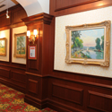 Hallway of gold framed paintings of landscapes.